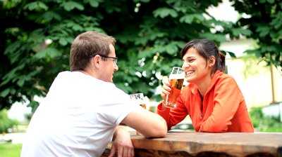 stock-footage-young-happy-couple-talking-laughing-and-drinking-beer-outdoors