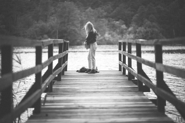 kaboompics.com_Alone girl standing on the wooden pier